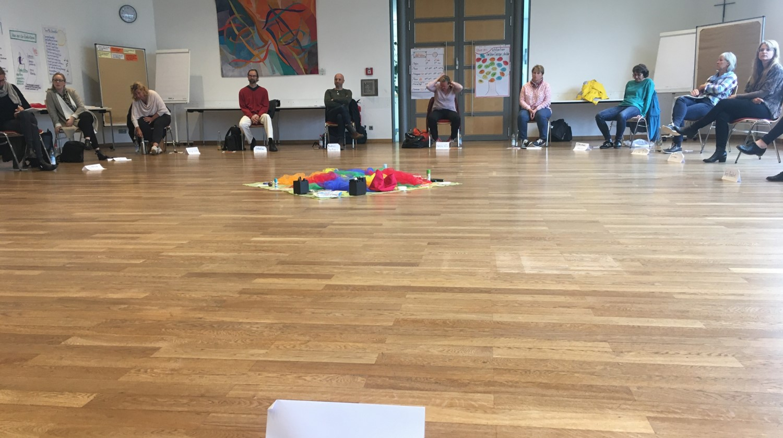 Teilnehmer sitzen im Seminar im Kreis